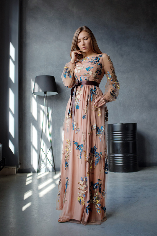 Бежевое платье с цветами поверх ткани.